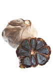 Black Garlic. Gourmet fermented black garlic, one bulb halved to show the segments stock photos