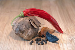 Black garlic. Bulb with hot pepper and black pepper grains Royalty Free Stock Photos