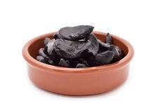 Black garlics in an earthenware bowl. Some black garlics in an earthenware bowl on a white background royalty free stock image
