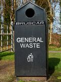 Black general waste metal bin in a park