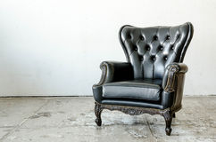 Black genuine leather classical style sofa. In vintage room Royalty Free Stock Image