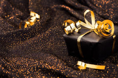 Black gift box on black shiny background. Royalty Free Stock Images