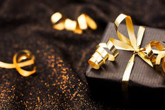 Black gift box on black shiny background. Royalty Free Stock Photos