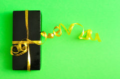 A black gift box with a gold ribbon Stock Photos