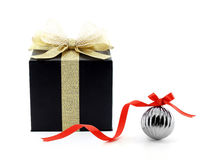 black gift box with golden ribbon and shining net bow and metallic glossy gray christmas ball with red ribbon bow isolated on whit Stock Photo