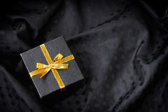 Black gift box with golden ribbon bow Royalty Free Stock Image