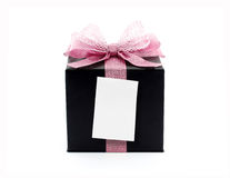 close up white note paper stick on black gift box with pink ribbon net bow isolated on white background Stock Photos