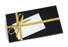 Black gift box (present) with golden ribbon bow and a blank card with copy space Royalty Free Stock Photo