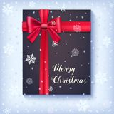 Black gift box with red bow and ribbon on snow backdrop.. Congratulations card of Marry Christmas on snowy and frosty background. Template for your cover Royalty Free Stock Photos