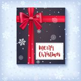 Black gift box with red bow and ribbon on snow backdrop. Congratulations card of Marry Christmas on snowy and frosty. Background. Template for your cover Royalty Free Stock Images