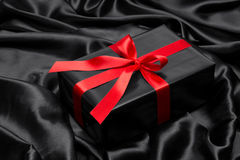 Black gift box with red satin ribbon and bow Stock Photo