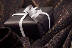 Black gift box on shiny background. Black gift box with silver bow on black shiny background Stock Photography