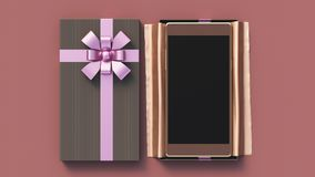 Black gift box with smartphone. Modern golden smartphone in small luxury black gift box, with purple ribbon and golden silk, on red background, top view. Concept Royalty Free Stock Photography