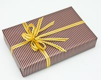Black gift box with white bar attached gold ribbon Royalty Free Stock Photos