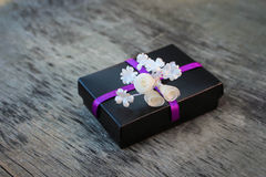 Black gift box with white flowers on the old wooden background Stock Photos