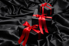 Black gift boxe with red satin ribbons and bow Royalty Free Stock Image