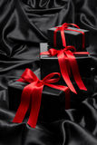 Black gift boxe with red satin ribbons and bows Stock Photo