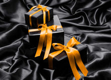 Black gift boxe with yellow satin ribbons Stock Image