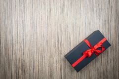 Black gift boxes with a bow on a wooden table. copy space royalty free stock images