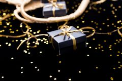 Black gift boxes with gold ribbon pop out from golden bag on shine background. Close up. Black gift boxes with gold ribbon pop out from golden bag on shine Stock Photo