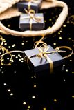 Black gift boxes with gold ribbon pop out from golden bag on shine background. Close up. Black gift boxes with gold ribbon pop out from golden bag on shine Royalty Free Stock Photography