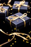 Black gift boxes with gold ribbon on shine background. Close up. Black gift boxes with gold ribbon on shine background. Close up Royalty Free Stock Photos