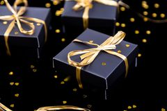 Black gift boxes with gold ribbon on shine background. Close up. Black gift boxes with gold ribbon on shine background. Close up Stock Photo