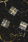 Black gift boxes with gold ribbon on shine background. Flat lay stock photography