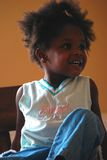Black Girl. A young girl is sitting on top of a table enjoying herself Royalty Free Stock Photography
