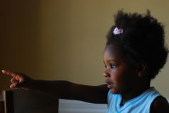 Black Girl. A young girl is pointing out the window at something that is interesting Stock Photography