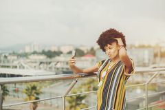 Black girl is aping while making selfie on the bridge. Naughty young black girl with curly afro hair in traditional suit is being goofy while making selfie near Royalty Free Stock Photography