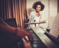 Black girl behind drums on a rehearsal. Black woman drummer in a recording studio stock photos