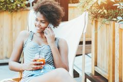 Black girl in cafe with smartphone and alcoholic beverage stock image