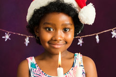 Black girl with christmas hat holding candle. Close up face shot of little afro american girl with christmas hat holding candles Royalty Free Stock Image