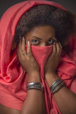 Black girl covering her face with rose cloth Royalty Free Stock Images