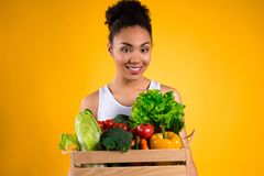 Black girl with crate of vegetables isolated. stock image