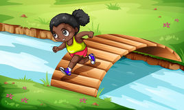 A black girl crossing the wooden bridge Stock Photos
