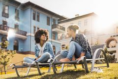 Friendly conversation of two girls of different races outdoor stock photos