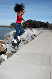 Black girl jumping by lake stock images