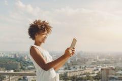 Black girl is making selfie on her digital tablet stock photo