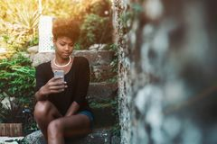 Black girl is making selfie while sitting in park. Admirable young Brazilian female is sitting on the stone step of staircase and taking selfie using camera of royalty free stock images