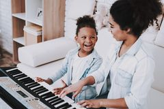Black Girl and Mother Play on Piano. Girl with Mom. stock image