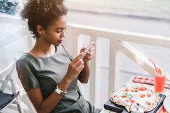 Black girl is posting food photo to her social networks. Dazzling Brazilian girl with curly Afro hair is photographing on her smartphone food in the cafe before royalty free stock photos