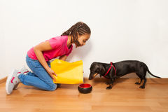 Black girl put food on dog plate Stock Image