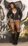 Black girl in sexy hooded outfit by graffiti wall. Sexy urban African-American  girl in boots, bra and hooded jacket standing by graffiti wall Royalty Free Stock Photos