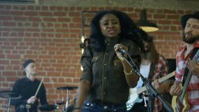 Black girl singing with band