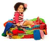 Black girl sitting in the basket with clothes Stock Photo
