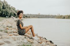 Black girl is sitting on stones of the embankment. Charming African-American girl is sitting on a stony quay of a river with the park and a walkway behind her Royalty Free Stock Photo