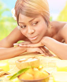 Black girl on spa resort. Attractive black woman relaxed on luxury spa resort, lying down on massage table with frangipani flower in hair on the beach in sunny stock photos