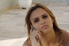 Black girl talks on cellphone. Beautiful woman talks serious on cellphone royalty free stock image